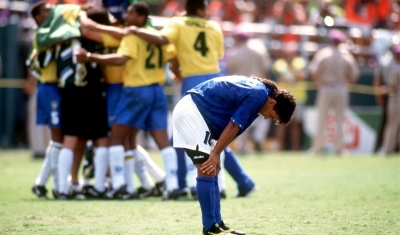 Roberto Baggio of Italy shows his disappointment after missing his penalty as Brazil celebrate